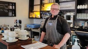 En man står bakom en disk på en restaurang.