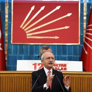 En politiker i talarstolen, Turkiets flagga i bakgrunden.