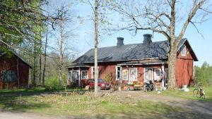 ett gammalt stockhus i rödmylla. Framför huset en bil och gamla möbler (loppisgrejer)
