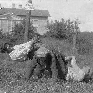 """Tre män leker """"lyfta saltsäck"""", där en person är på alla fyra på marken, och de två andra är på hans rygg medan den första försöker stiga upp. Bilden är tagen 1930 i Bromarf."""
