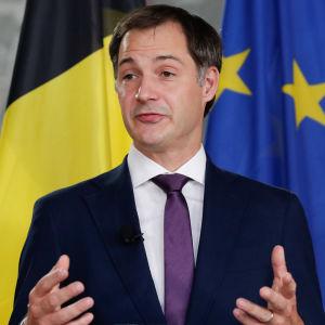 Alexander De Croo håller presskonferens. I bakgrunden Belgiens och EU:s flaggor.