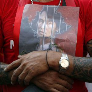 En man håller ett foto av Mynamars fängslade valda ledare Aung San Suu Kyi mot bröstet.