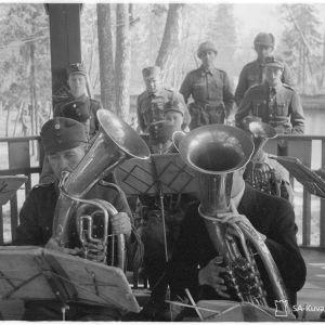 Militärklädda män spelar blåsinstrument på en terass. Bilden är gammal och svartvit.
