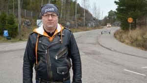 En man iklädd svartskinnjacka står på en väg.