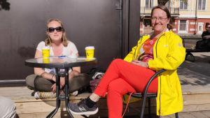 Två kvinnor sitter vid ett bord utomhus.