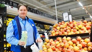 En medelålders man i blå skjorta håller i en rulle med biopåsar. Han står bredvid en hylla med päron.