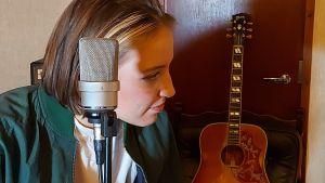Ilon, mikrofon och gitarri bakgrunden. Ansiktet i profil.