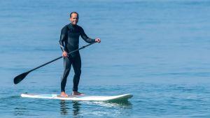 En glad man i mörk våtdräkt på en paddelbräda i ett blått hav. Han har en paddel i handen. Solen skiner. Sportig stämning.