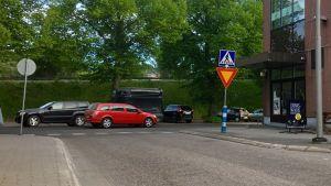 En T-korsning mellan två gator. Bilar kör och andra bilar står parkerade bakom korsningen. I bakgrunden en grön bank och gröna lövträd. Trafikmärken.