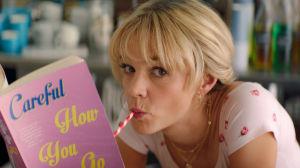 Närbild på Cassandra (Carey Mulligan) som suger på ett sugrör.