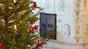Till vänster synns en juklgran med röda prydnader. Den står framför en vit kakelugn med färggranna fjärilar och blommor på.