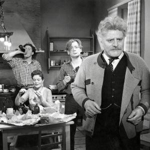 Professori kääntää selkänsä pöydän ääressä mässäilevälle perheelle elokuvassa Kuriton sukupolvi.