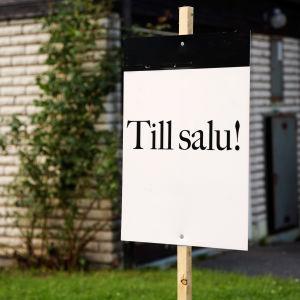 """En """"Till salu""""-skylt utanför ett hus."""