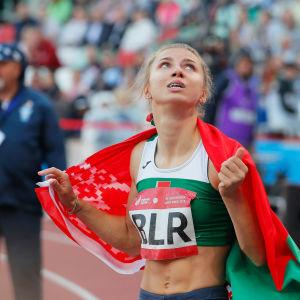 Kristina Timanovskaja tittar uppåt med den belarusiska flaggan.