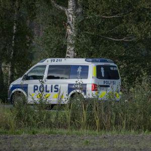 En polisbil vid en grusväg.