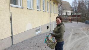 kvinna står utanför skola