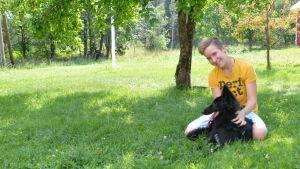 en flicka sitter på gräsmattan med sin svarta hund.