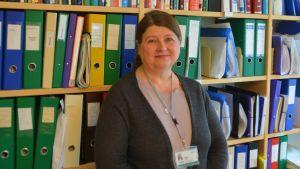 Kvinna framför en bokhylla.