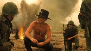 Bill Kilgore (Robert Ruvall) sitter på huk på en sandstrand omgiven av soldater och explosioner.