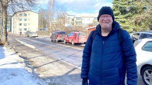 En man i blå jacka står på en gata och ler i vårsolen.