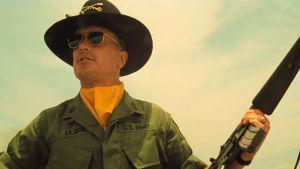 Bill Kilgore (Robert Ruvall) står med ett gevär i handen och ser nöjd ut.