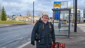 En kvinna med en röd kasse i handen står vid en busstation i Nickby.