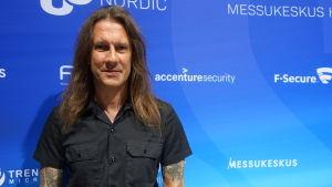 En man med långt mörkt hår och ser rakt in i kameran. Han är tatuerad och står framför en blå vägg