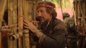 Fotojournalisten (Dennis Hopper) står vid ett bambustängsel.