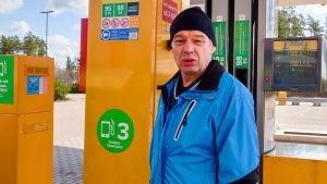 Man i blå jacka står framför orange bensinpump.