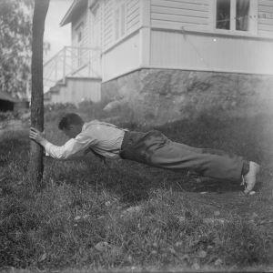 En man lutar mot en trädstam och sträcker ut sig vilande på sina tår. Bilden är tagen 1930 i Bromarf.