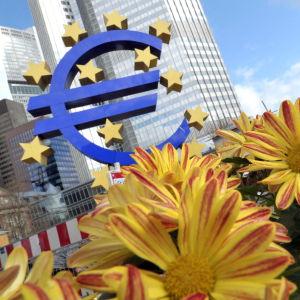 Blommor och eurotecken framför Europeiska centralbanken.