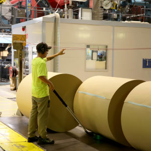 työntekijä käsittelee laminaattipaperirullia