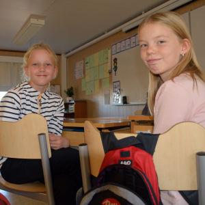 Två flickor sitter i ett klassrum vid sina pulpeter.