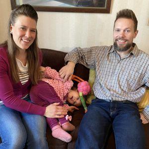 Hovien perhe istuu yhdessä sohvalla: Iidan ja Miikan välissä temppuilee Hulda.