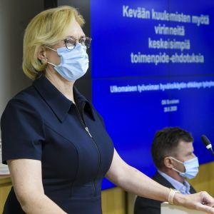 Tuula Haatainen med munskydd vid presskonferens