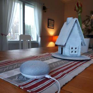 En smart högtalare på ett bord med en julduk. En lykta i form av en stuga i bakgrunden.