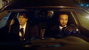 Mikko Nousiaisen ja Jari Virmanin esittämät hahmot istuvat ruumisautossa etupenkillä.