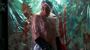Robert Enckellin näyttelemä mies seisoo verisessä huoneessa jokin paloitteluase käsissään, muovivaate yllään. Hiljaisten palvelijat -sarjasta.