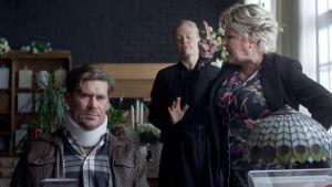 Tommi Korpelan esittämä hahmo istuu tuolilla niskatuki yllään. Tiina Weckströmin esittämä hahmo seisoo hänen vieressään vihaisena etusormeaan heiluttaen.