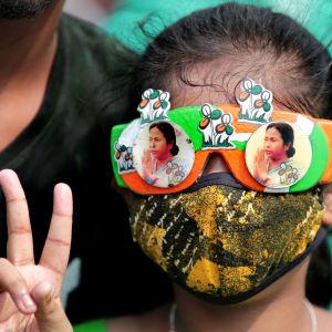 En anhängare till TMC-partiet i Västbengalen visade upp segertecknet, iklädd glasögon prydda av porträtt på partiledaren Mamata Banerjee.