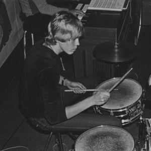 Nuori vaaleahiuksinen mies soittaa rumpuja keskittyneesti