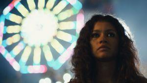 Huvudkaraktären Rue stirrar planlöst förbi kameran med glitter under ögonen och ett lysande Pariserhjul i bakgrunden.