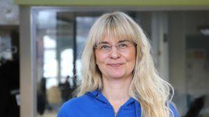 En kvinna med långt ljust hår, glasögon och en klarblå blus.