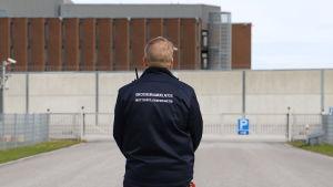 En man i uniform står utanför porten till Åbo fängelse med ryggen vänd mot kameran..