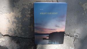 """En bok som vilar mot en betongvägg. Bokens titel är """"Något har hänt""""."""
