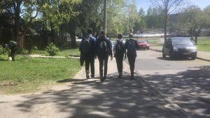 Fyra ryska skolungdomar går hem efter skolan, fotade bakifrån