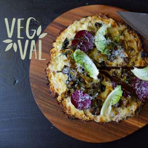 En blomkålspizza på ett på ett rund skärbräde.