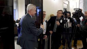Journalister på sin vakt då Pekka Haavisto öppnar dörren till grundlagsutkottets mötesrum.
