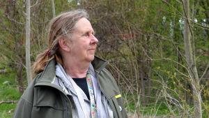 Kristina Renqvist mot bakgrund av skogssnår.
