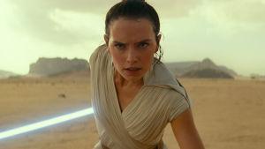 Närbild på Rey (Daisy Ridley) som stirrar rakt fram och har sitt lasersvärd redo bakom sig.